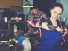 woman master is standing with adjustable wrench in workshop.