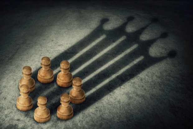 Chess pawn standing together, arranged in a circle joining the power, casting a crown shaped shadow. Business group leadership and team working concept. Belief in success.