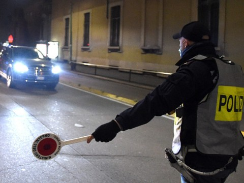 MILAN, ITALY - APRIL 04:  A policeman stops  a car during a night checkpoint for the control of the territory during the coronavirus outbreak on April 04, 2020 in Milan, Italy. The Italian government continues to enforce the nationwide lockdown measures to control the spread of COVID-19.  (Photo by Pier Marco Tacca/Getty Images)